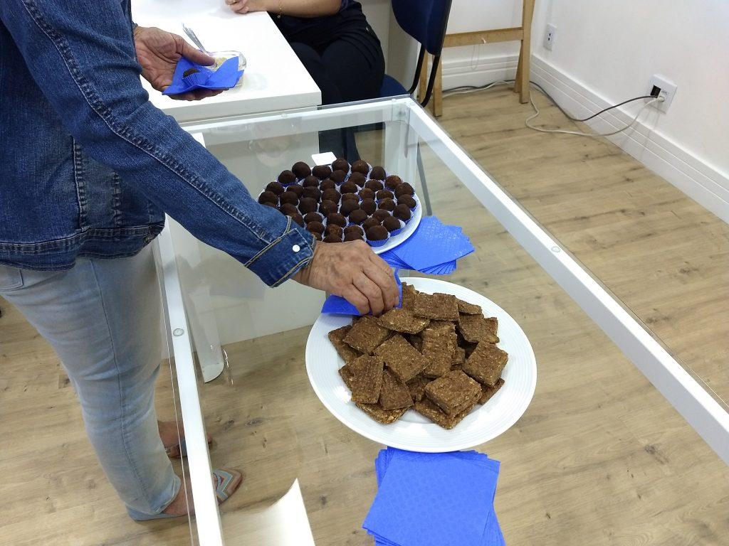 na foto há dois pratos de docinhos da do chocolate, uma pessoa está se servindo