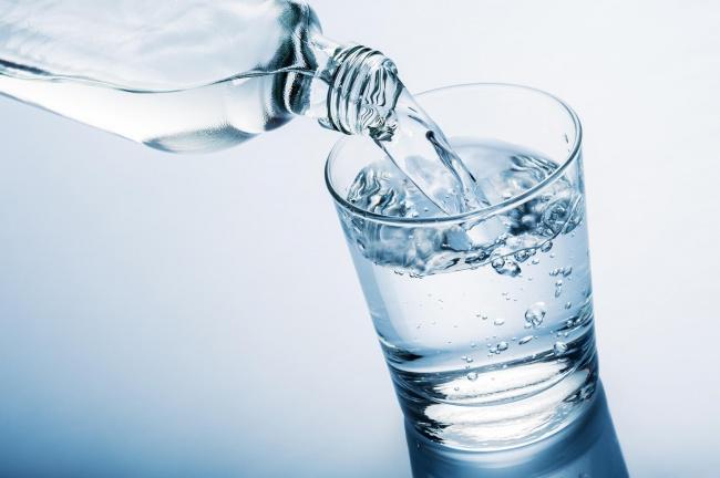 foto de uma garrafa de agua mineral sorvando em um copo de vidro representando a rotina na terceira idade