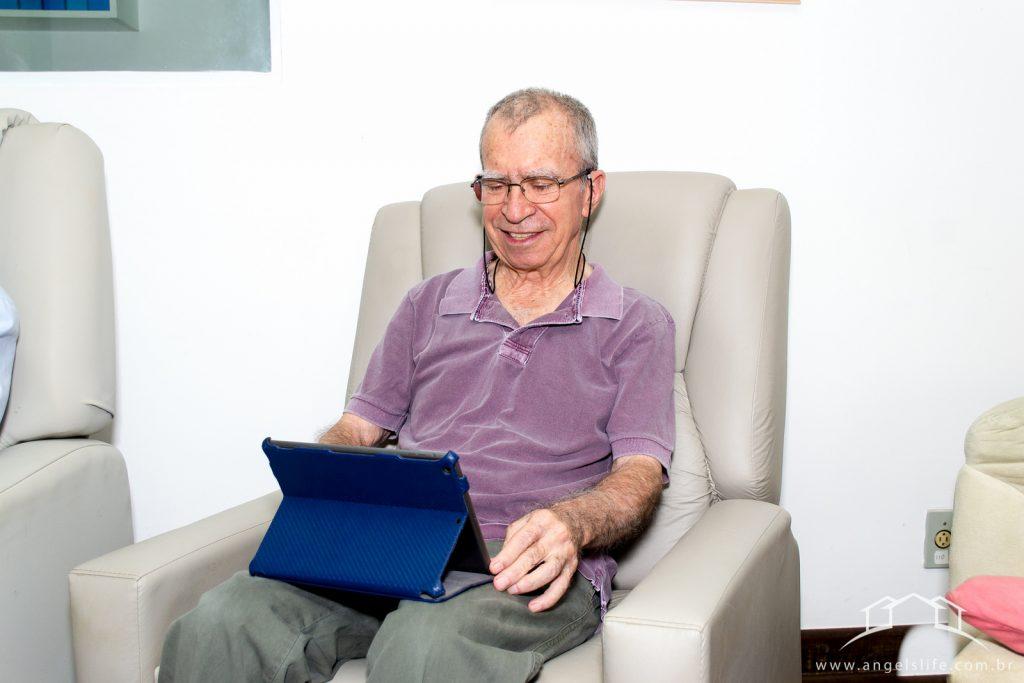 sr galvao, portador de parkinson, fazendo uma leitura em seu iPad