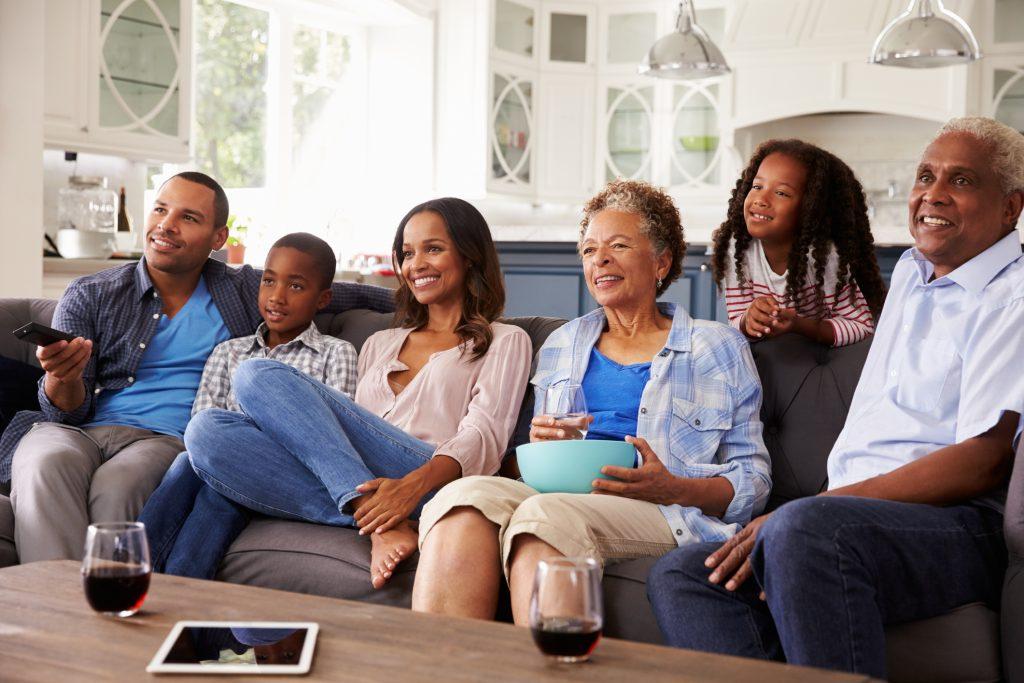 Familia multigeracional vendo fotos em uma TV