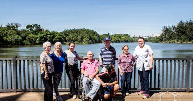 idosos apoiados em grade do deck do parque portugal em campinas, eles estao sorrindo para a foto juntamente com uma terapeuta ocupacional um motorista e uma acompanhante